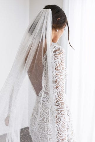 Back shot of bride wearing Grace Loves Lace Shimmy Veil in Ivory Gold looking at the floor