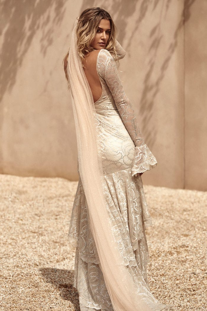 Back shot of bride wearing Grace Loves Lace Shimmy Veil in Nude Gold looking over shoulder walking along beach