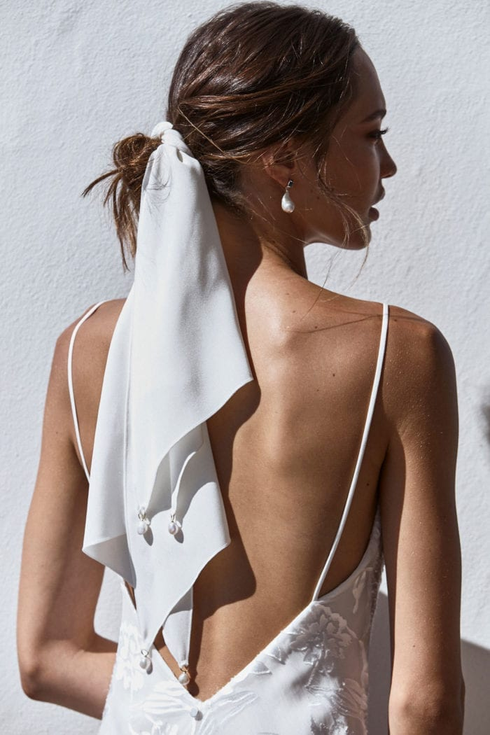 Back shot of bride wearing Grace Loves Lace Pope Silk Scarf wrapped around hair
