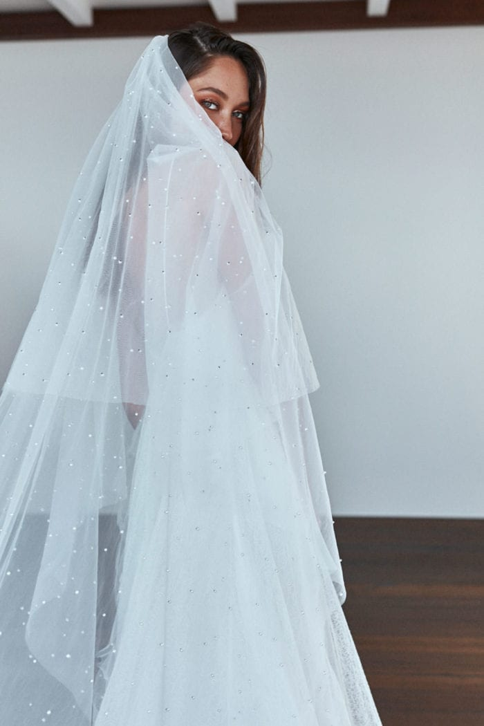 Back shot of bride wearing Grace Loves Lace Pearly Blusher Veil draped over her shoulders