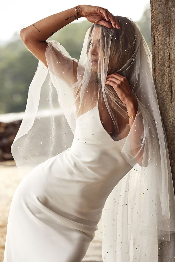 Bride wearing the Grace Loves Lace Pearly Blusher Veil draped over her face leaning against a wooden post