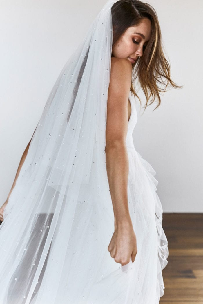 Back shot of bride wearing Grace Loves Lace Pearly Blusher Veil looking behind her