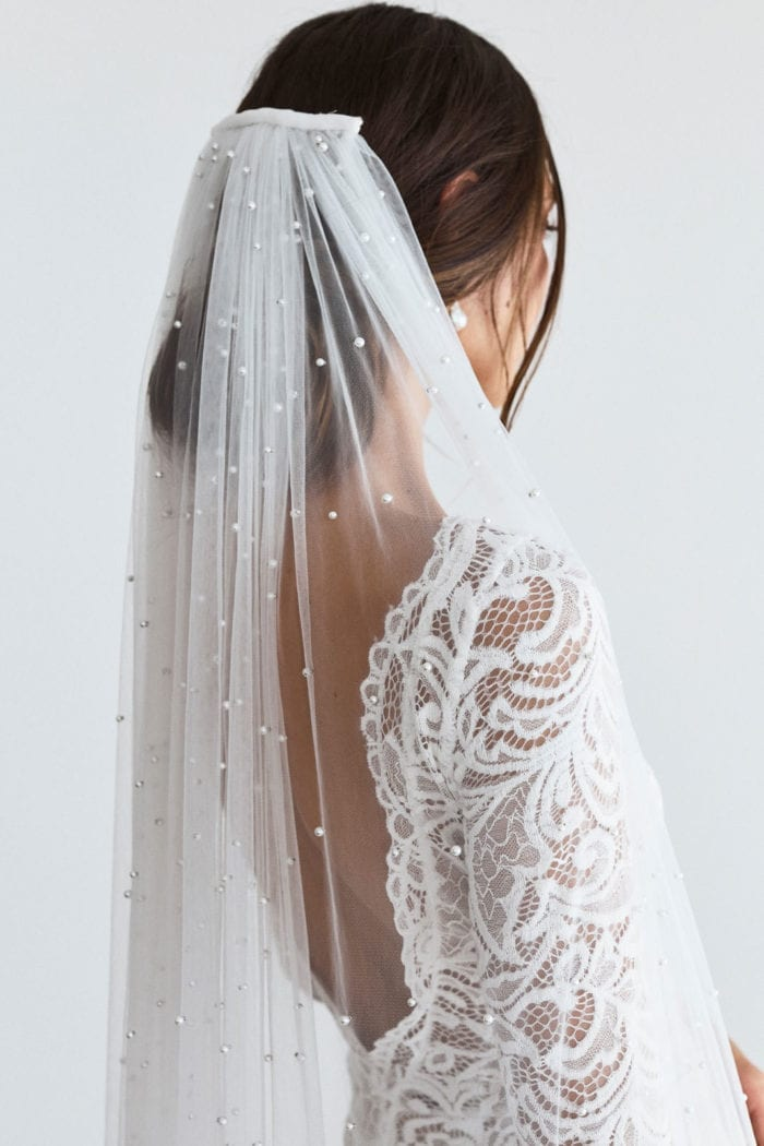 Back shot of bride wearing Grace Loves Lace Pearly Long Veil clipped into her hair