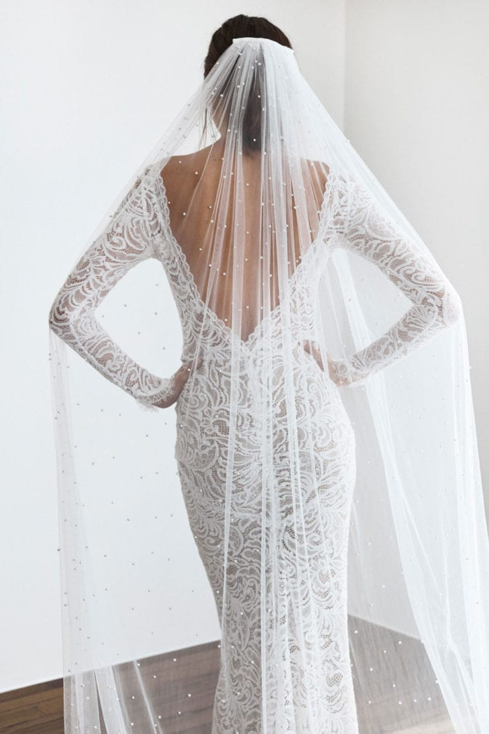 Back shot of bride wearing Grace Loves Lace Pearly Long Veil with both hands on her hips