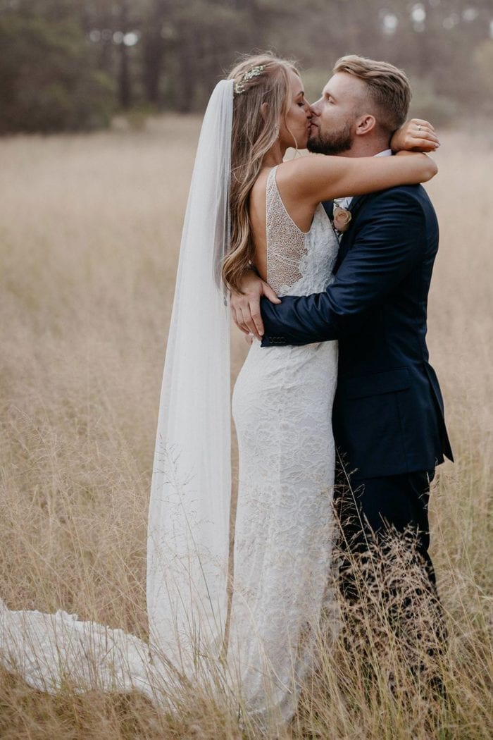 Side shot of bride wearing Grace Loves Lace Mandala Veil kissing groom in a field