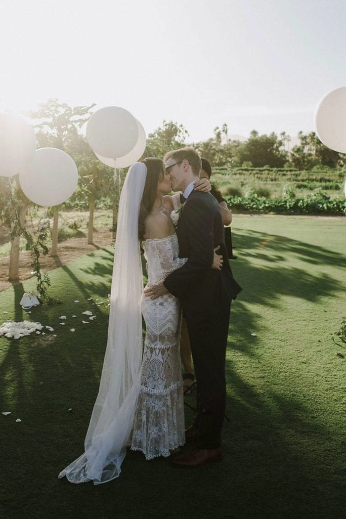 Side shot of bride wearing Grace Loves Lace Mandala Veil kissing groom in garden