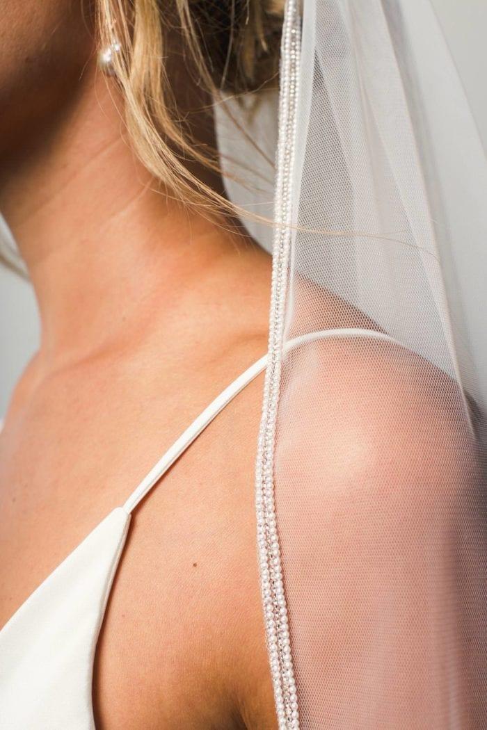 Close-up shot of bride wearing Grace Loves Lace Mandala Veil and pearl earrings
