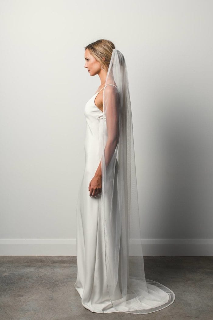 Side shot of bride wearing Grace Loves Lace Mandala Veil draped over shoulders