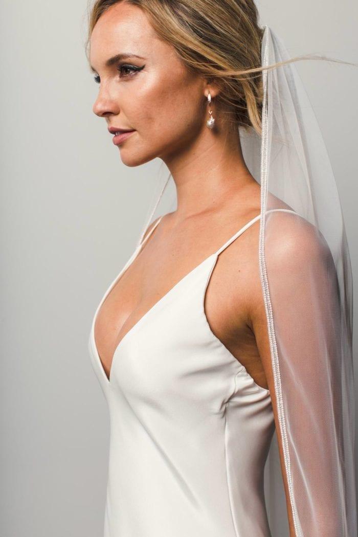Side shot of bride wearing Grace Loves Lace Mandala Veil and pearl earrings