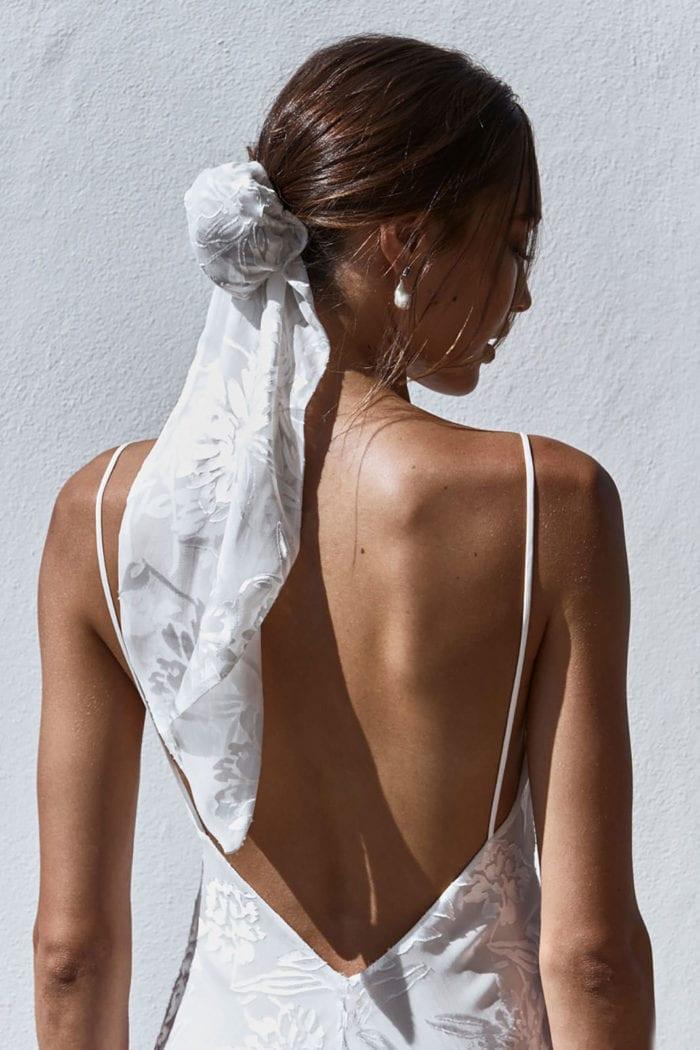 Back shot of bride wearing Grace Loves Lace Loyola Hair Bun and pearl earrings