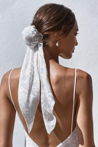 Back shot of bride wearing Grace Loves Lace Loyola Hair Bun and pearl earrings