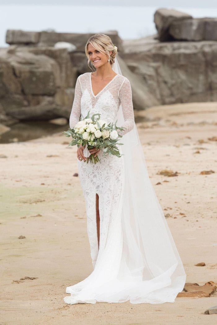 Bride wearing Grace Loves Lace Kinga Veil standing on a beach holding bouquet