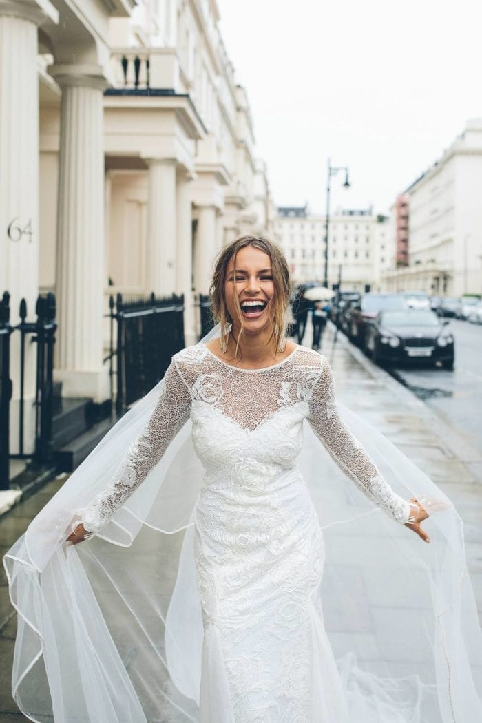 Bride wearing Grace Loves Lace Kinga Veil holding veil in both hands on rainy street