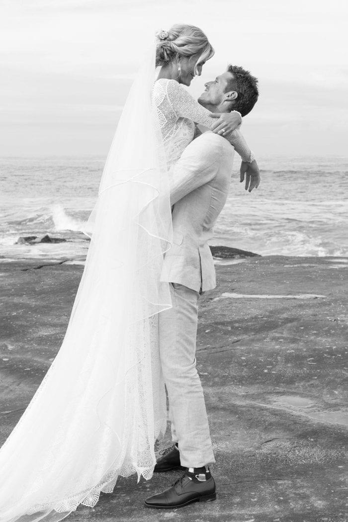 Bride wearing Grace Loves Lace Kinga Veil being held by groom on beach