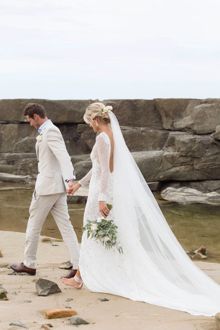 Bride wearing Grace Loves Lace Kinga Veil holding hands with groom walking along beach