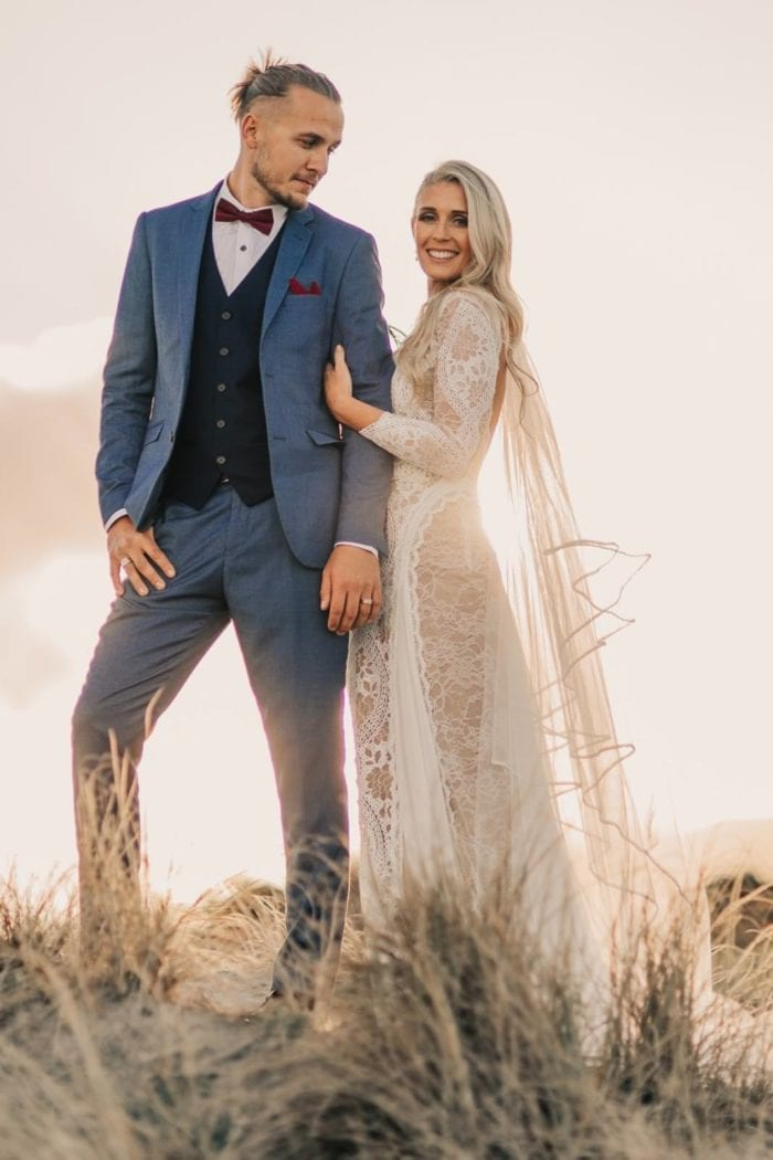 Bride wearing Grace Loves Lace Kinga Veil holding groom's arm surrounded by long grass