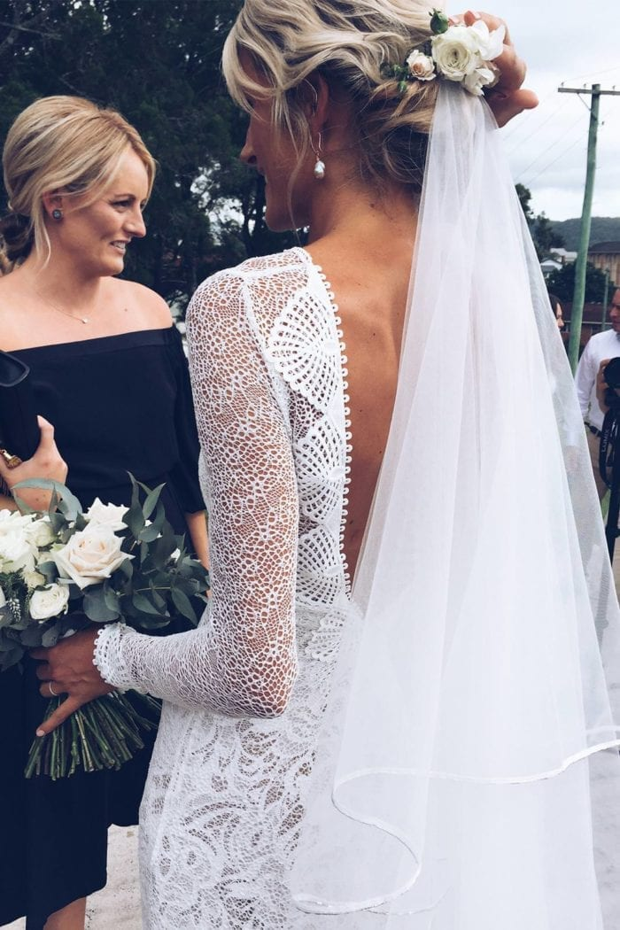 Back shot of bride wearing Grace Loves Lace Kinga Veil and flowers in hair holding bouquet