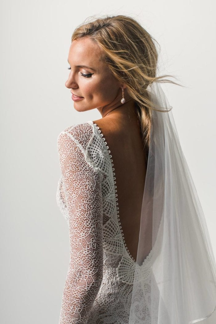 Back shot of bride wearing Grace Loves Lace Kinga Veil and pearl earrings