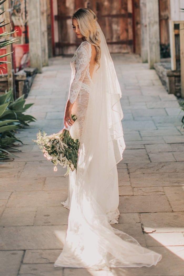 Back shot of bride wearing Grace Loves Lace Kinga Veil holding bouquet