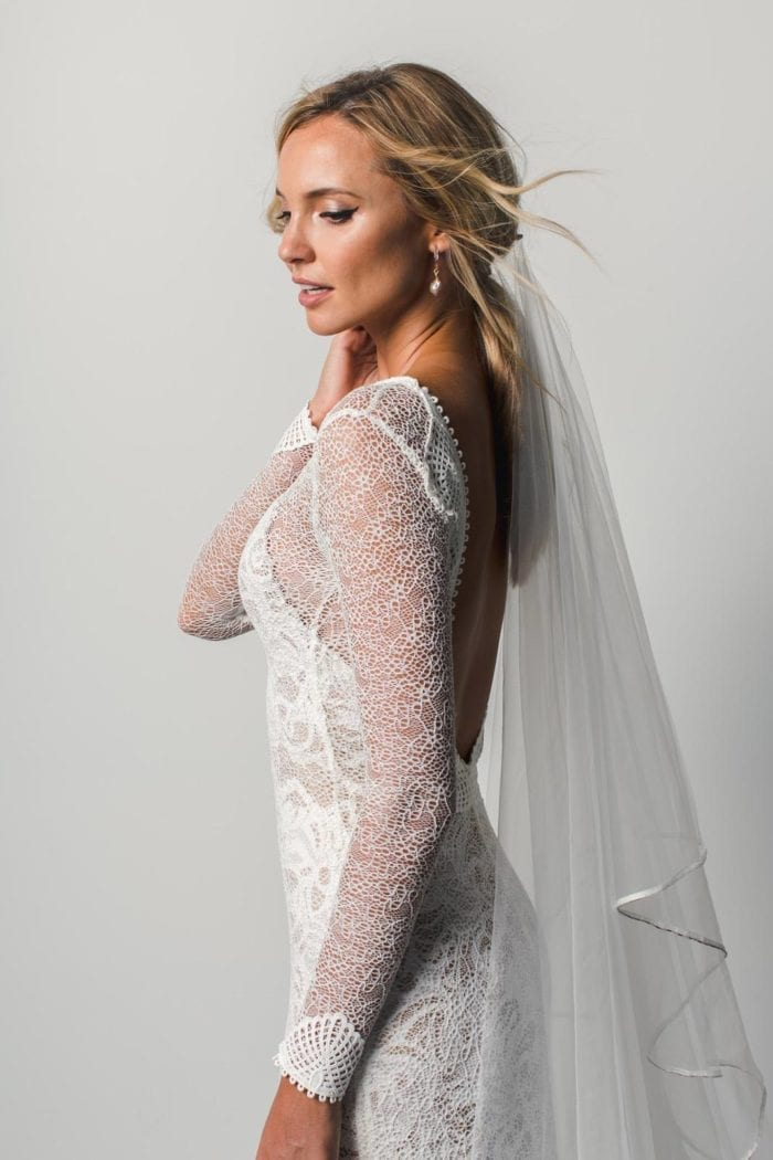 Side shot of bride wearing Grace Loves Lace Kinga Veil and pearl earrings with hand on hair
