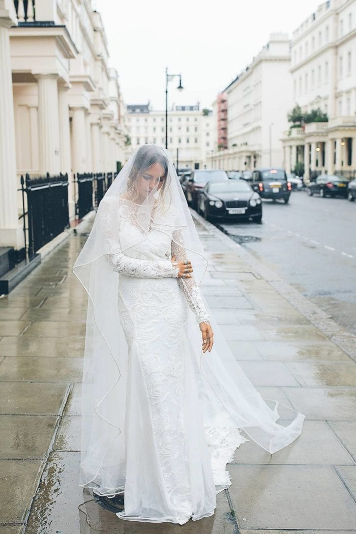Bride wearing Grace Loves Lace Kinga Veil over face in rainy street