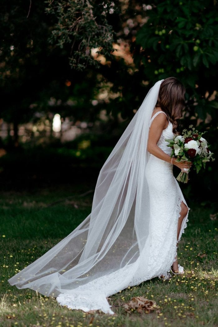Bride wearing the Grace Loves Lace Henri Veil in garden holding a bouquet