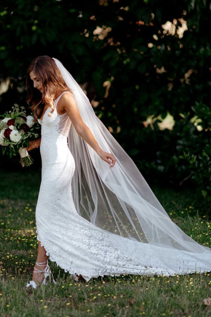 Bride wearing the Grace Loves Lace Henri Veil holding bouquet in garden