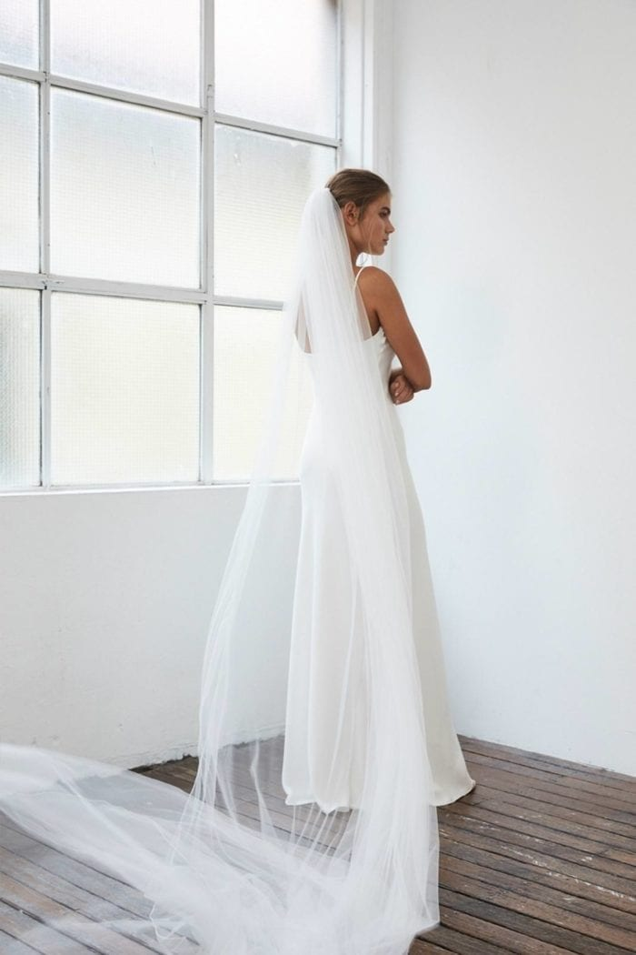 Back shot of bride wearing the Grace Loves Lace Henri Veil with arms folded