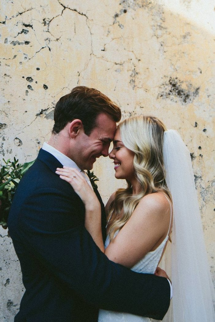 Bride wearing the Grace Loves Lace Henri Veil embracing groom