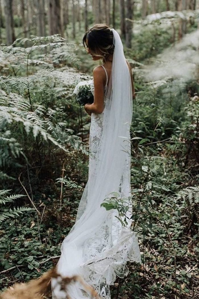 Back shot of bride wearing the Grace Loves Lace Henri Veil in a forest