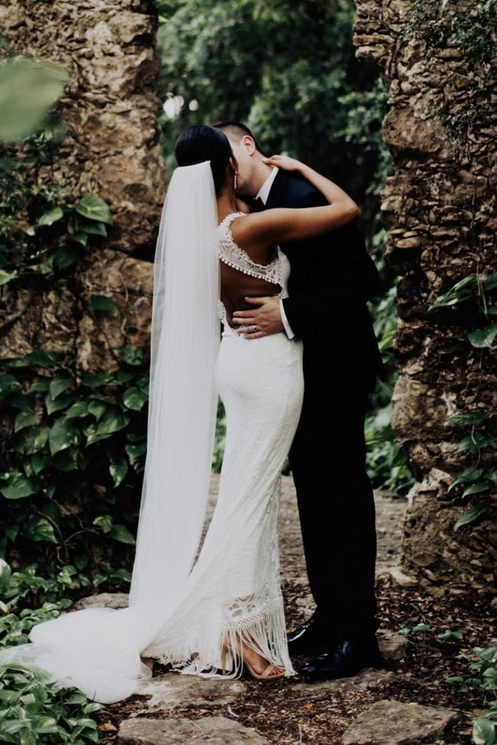 Bride wearing the Grace Loves Lace Henri Veil kissing groom in forest