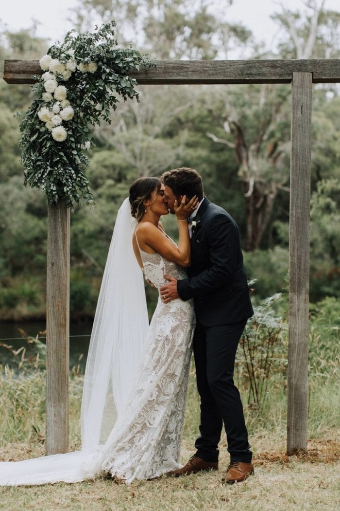 Bride wearing the Grace Loves Lace Henri Veil kissing groom under garden arch