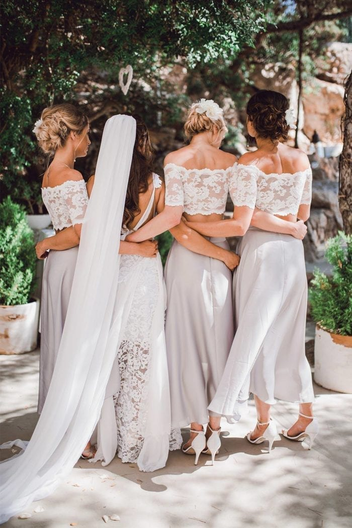 Back shot of bride wearing Grace Loves Lace Gabriela Veil interlocking arms with three bridesmaids
