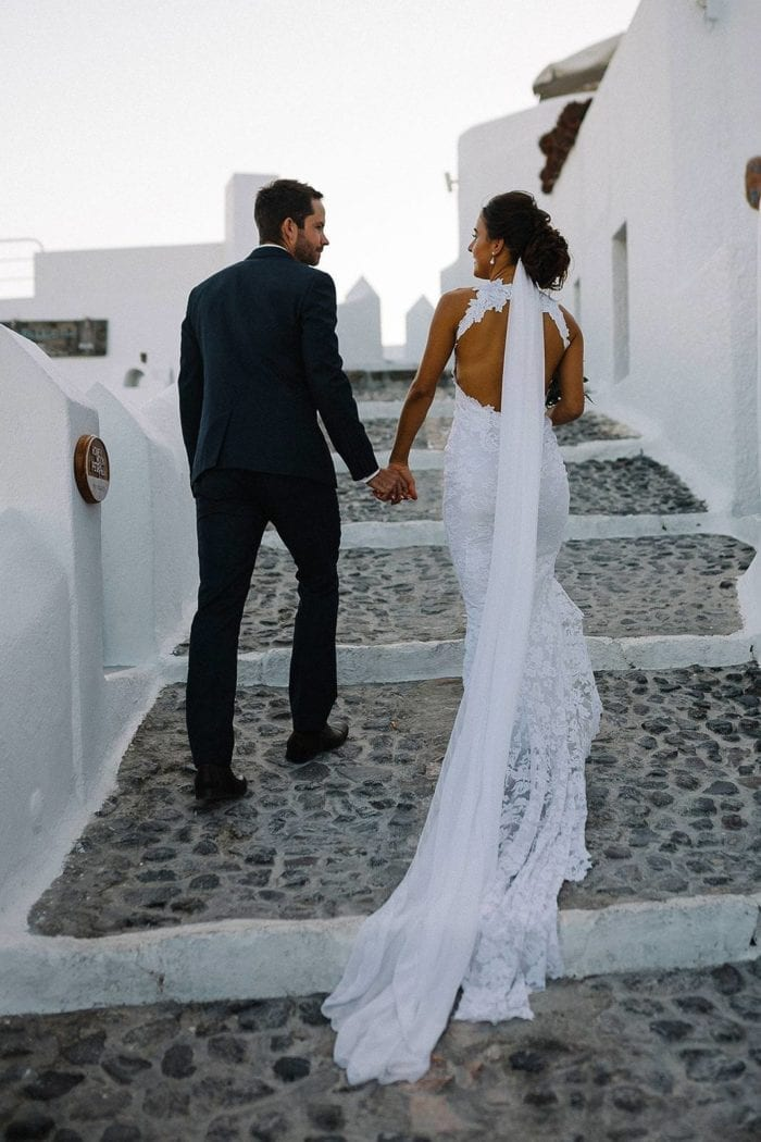 Bride wearing Grace Loves Lace Gabriela Veil while holding hands with groom as they walk up stairs