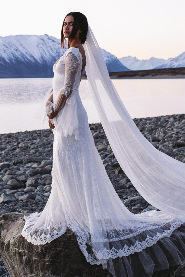 Bride wearing Grace Loves Lace Gabriela Veil as she stands on a pebbled beach