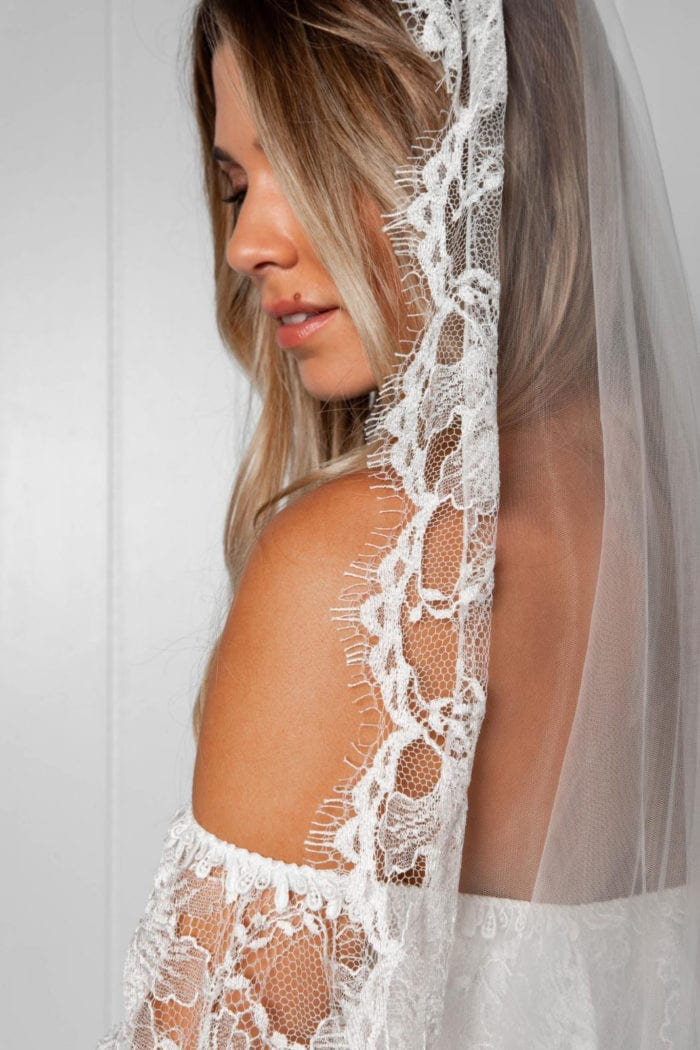 Close-up back shot of bride wearing Grace Loves Lace Frederike Veil looking over shoulder