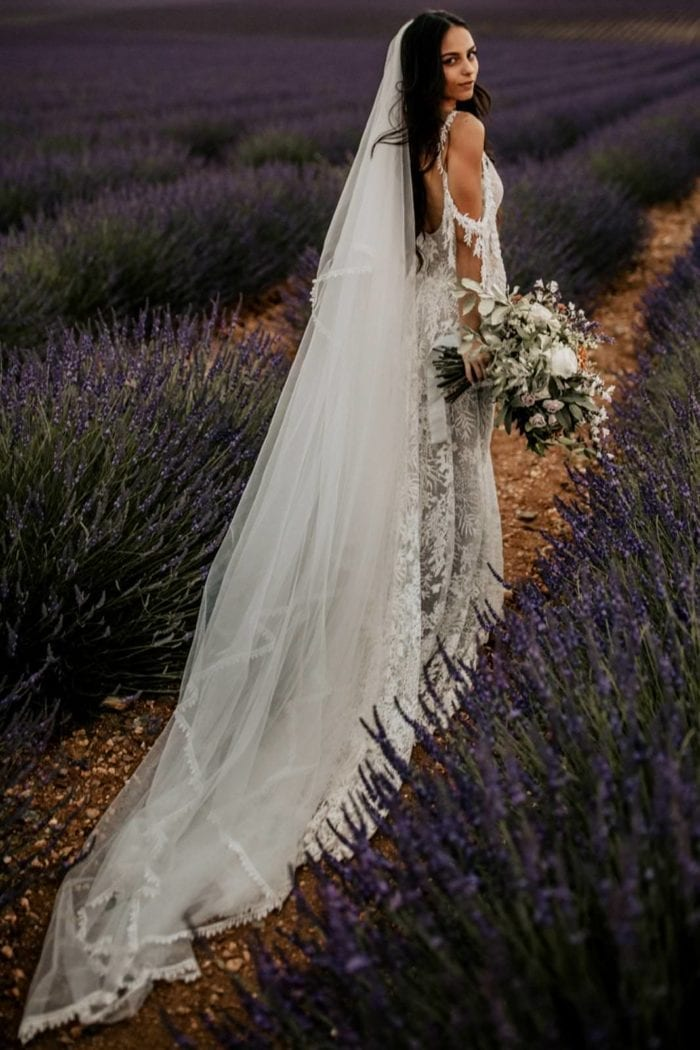Bride wears Grace Loves Lace Fox Veil in a field of lavender while holding a bouquet