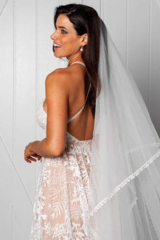 Back shot of bride wearing Grace Loves Lace Fox Veil and pearl earrings looking over shoulder