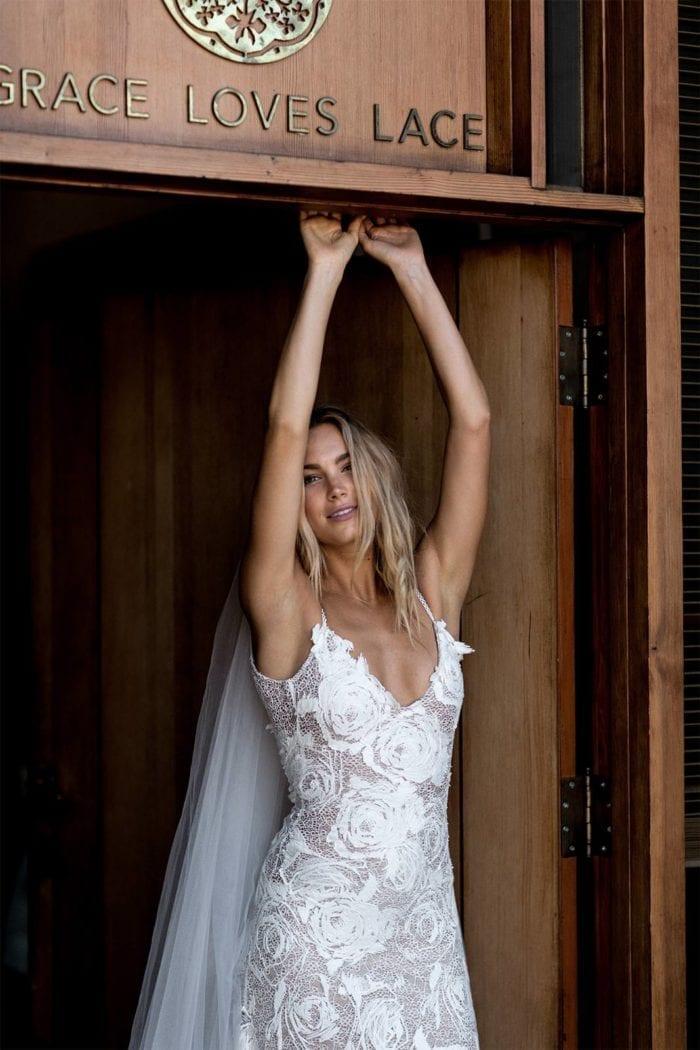 Bride wearing Grace Loves Lace Fleur Veil reaching up in doorway