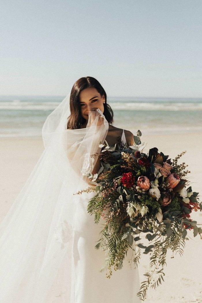 Bride wearing Grace Loves Lace Fleur Veil smiling on a beach holding a bouquet