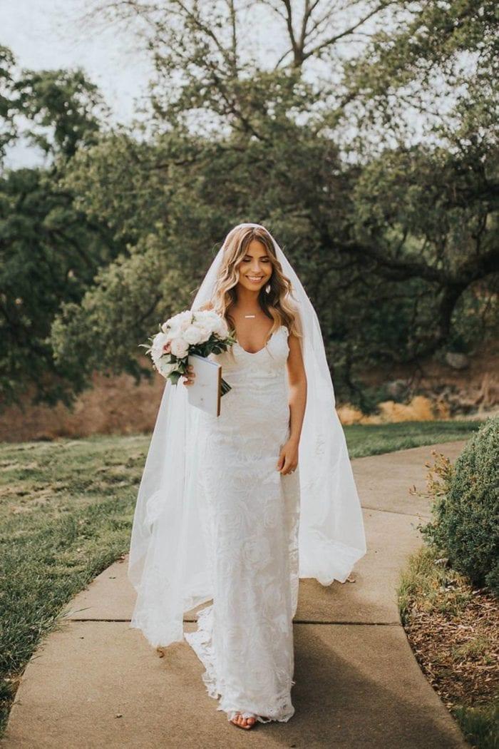 Bride wearing Grace Loves Lace Fleur Veil holding a bouquet and book