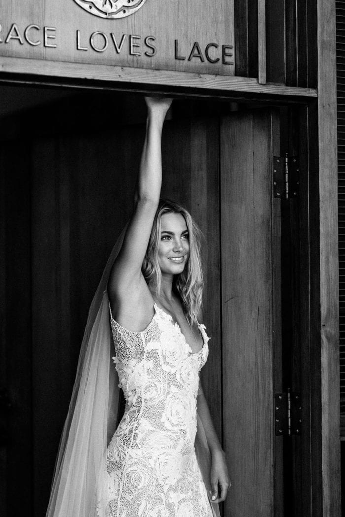 Black and white shot of bride wearing Grace Loves Lace Fleur Veil reaching up in doorway of Grace Loves Lace