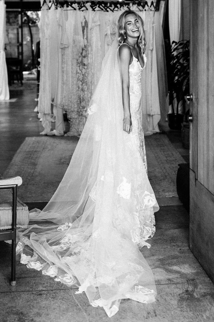 Black and white shot of bride wearing Grace Loves Lace Fleur Veil with dresses on the racks behind her