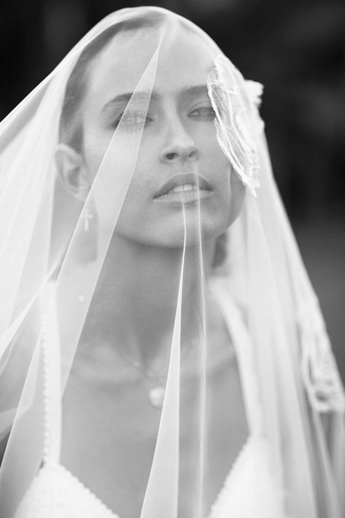 Close-up shot of bride wearing Grace Loves Lace Fleur Veil over face