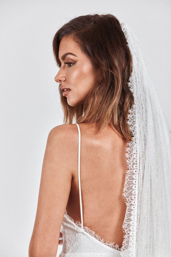 Back shot of bride wearing Grace Loves Lace Chantilly Veil looking to the side