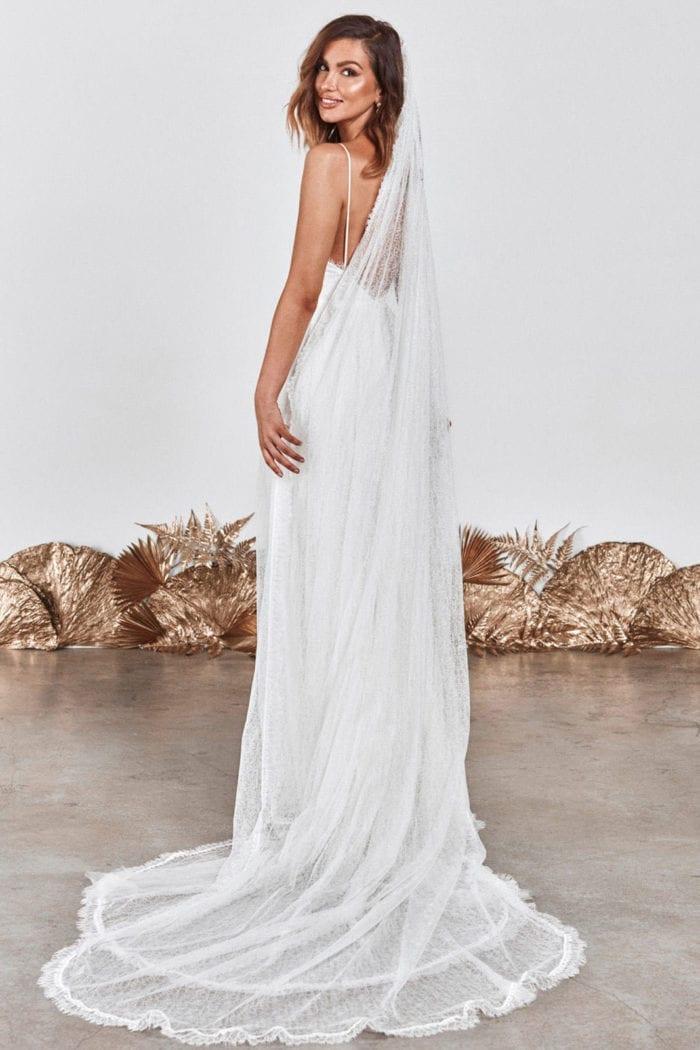 Back shot of bride wearing Grace Loves Lace Chantilly Veil looking over shoulder