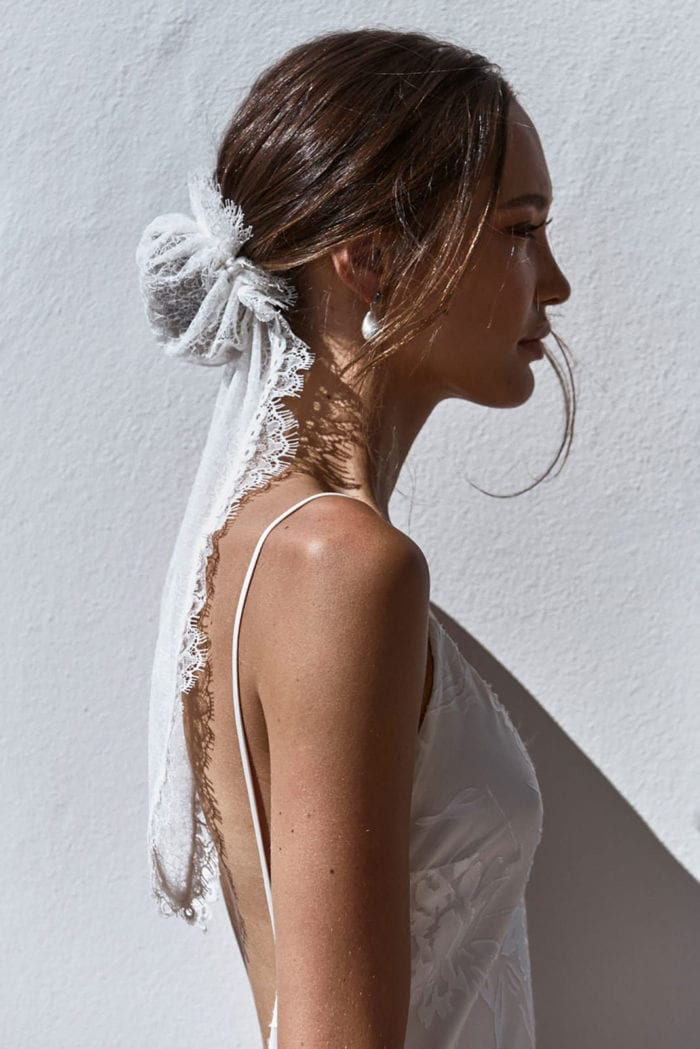 Side shot of bride wearing Grace Loves Lace Chantilly Bun and pearl earrings