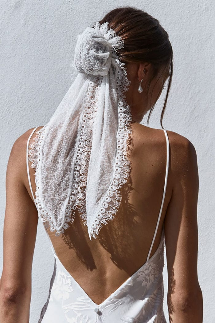 Back shot of bride wearing Grace Loves Lace Chantilly Bun and pearl earrings