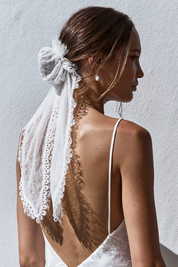 Back shot of bride wearing Grace Loves Lace Chantilly Bun and pearl earrings looking to the side